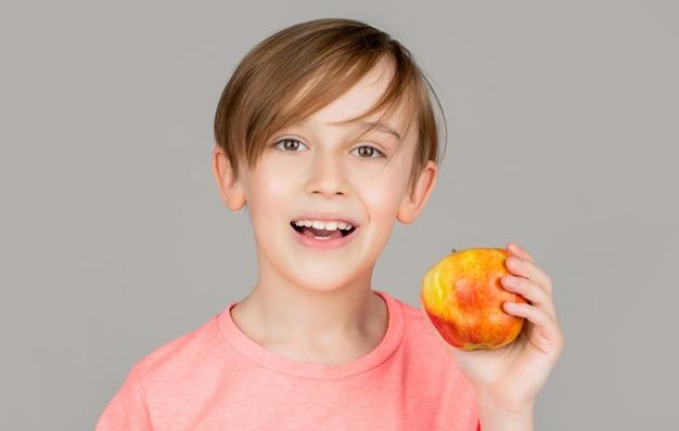 Ragazzino che mangia mela. mele del ragazzo che mostrano. bambino con le mele. ritratto di un ragazzino carino che tiene in mano una mela
