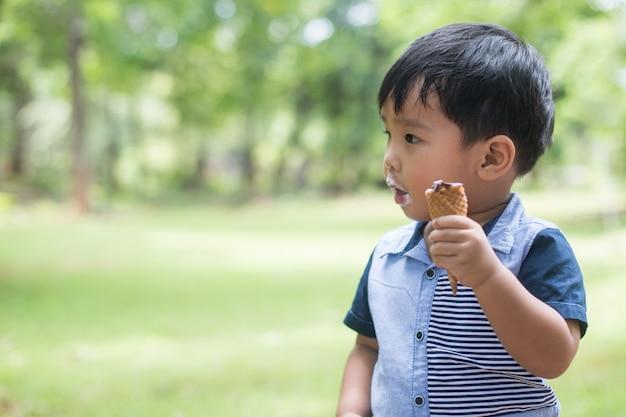 Ragazzino che mangia il gelato al campo da giuoco con tempo felice.