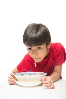 Ragazzino che mangia spaghetti istantanei su bianco