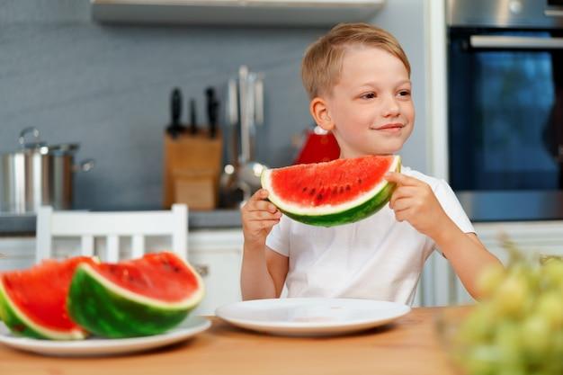 Ragazzino che mangia pezzo di anguria in cucina
