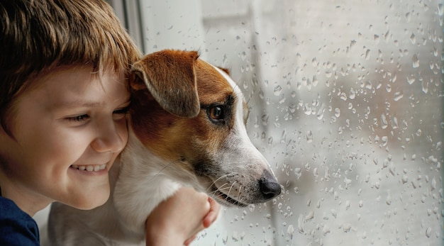 Ragazzino che abbraccia il cane sulla finestra concetto di nuovo anno di felicità di cura di amicizia