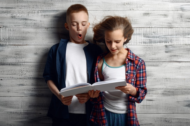 Ragazzino e ragazza stanno reding un libro contro il potente flusso d'aria in studio, sviluppando i capelli, effetto ventoso. bambini e vento, bambini isolati su fondo in legno, emozione bambino
