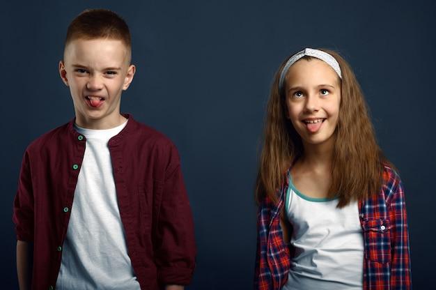 Ragazzino e ragazza che fanno i fronti. infanzia felice, bambini che si divertono, bambini divertenti isolati su sfondo scuro, emozione del bambino