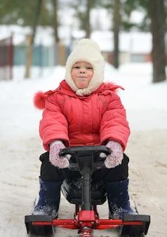 Ragazzino e ragazza scivolano giù dalla collina di neve su una slitta