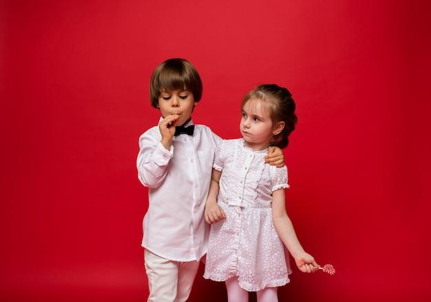 Ragazzino e ragazza con lecca-lecca su colore rosso
