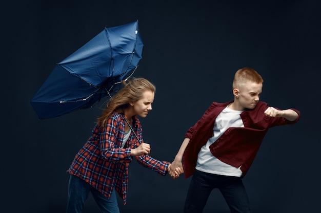 Ragazzino e ragazza con l'ombrello contro il potente flusso d'aria in studio, effetto vento, ventoso. bambini con peli in via di sviluppo, bambini isolati su sfondo scuro, emozione del bambino