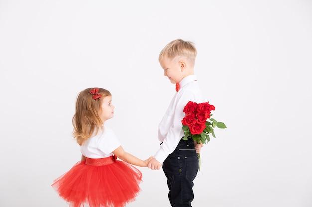 Ragazzino che dà il mazzo delle rose alla ragazza del bambino il giorno di biglietti di s. valentino su fondo bianco.