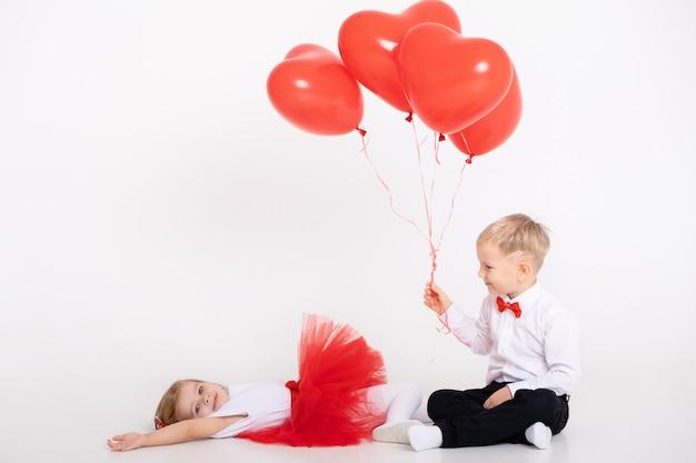 Ragazzino che dà palloncini cuore alla ragazza del bambino il giorno di san valentino