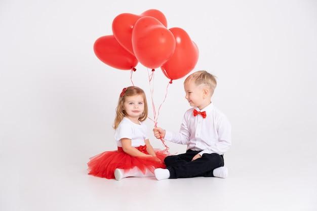 Ragazzino che dà palloncini cuore alla ragazza del bambino il giorno di san valentino sul muro bianco.