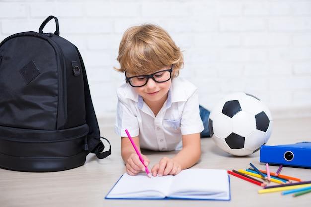 Ragazzino con gli occhiali che fa i compiti sdraiato sul pavimento