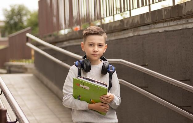 Ragazzino che torna a scuola. bambino con zaino e libri
