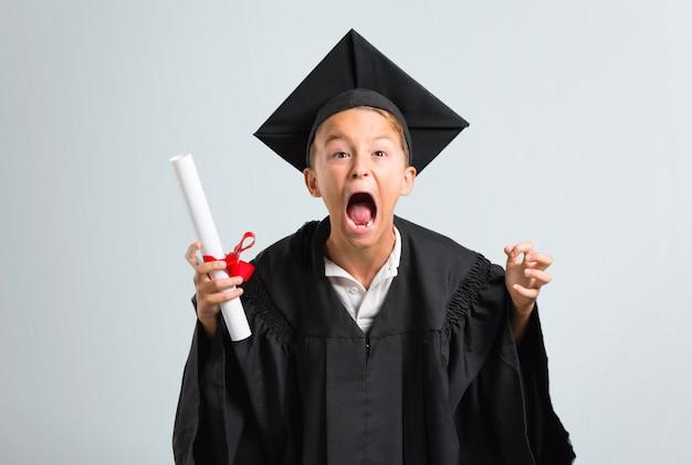 La laurea del ragazzino si è infastidita arrabbiata nel gesto furioso su fondo grigio