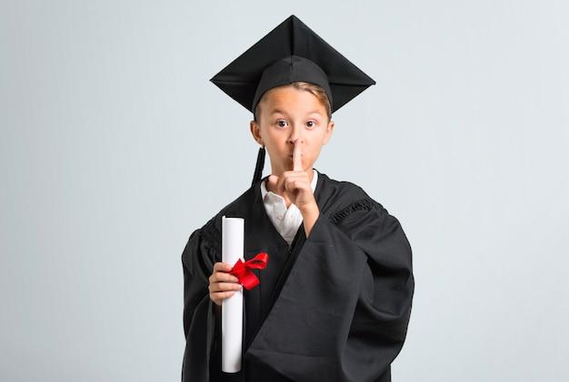 Ragazzino che si laurea mostrando un segno della bocca di chiusura e del gesto di silenzio su fondo grigio