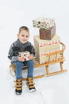Ragazzino in maglione lavorato a maglia grigio, seduto sulla slitta di legno, decorato con scatole con regali