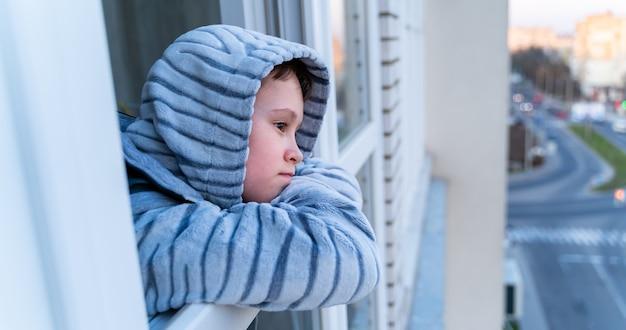 Ragazzino in pigiama grigio che guarda attraverso la finestra