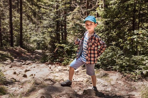 Il ragazzino con il berretto verde mostra un dito nel bosco