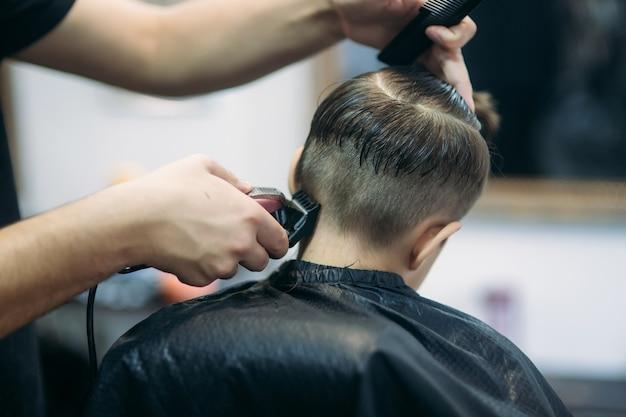 Il ragazzino su un taglio di capelli dal barbiere si siede su una sedia