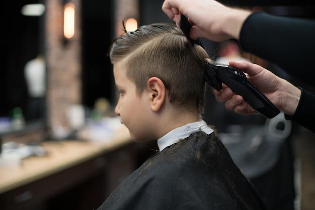Ragazzino su un taglio di capelli nel barbiere si siede su una sedia.