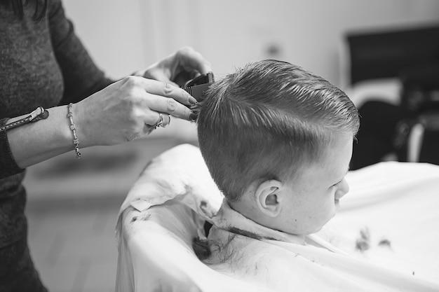 Ragazzino dal parrucchiere. il bambino ha paura dei tagli di capelli. mani del parrucchiere che fanno acconciatura al ragazzino, si chiuda. taglio di capelli alla moda per ragazzi.