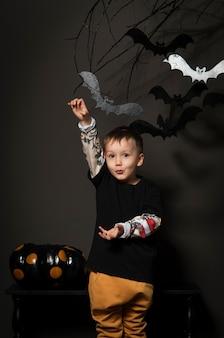 Ragazzino alla festa di halloween su sfondo nero con zucche e pipistrelli su un albero