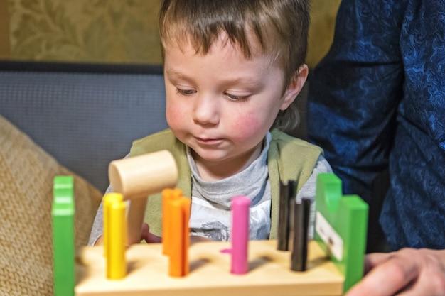 Ragazzino che martella chiodi giocattolo nella tavola di legno con il martello