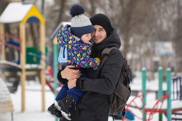 Il ragazzino nelle mani di suo padre nel clima invernale. passeggiata nel parco nella neve.
