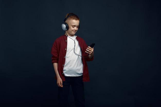 Il ragazzino in cuffia ascolta la musica
