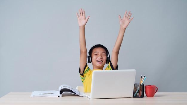 Ragazzino in cuffie che studiano in linea facendo uso del computer portatile