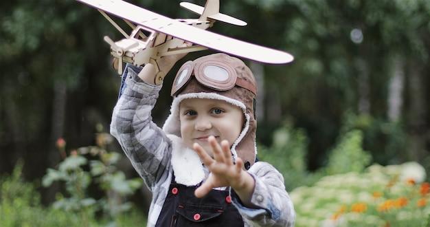 Un ragazzino in casco aviatore pilota di aereo gioca con un aereo di legno il bambino sogna di volare