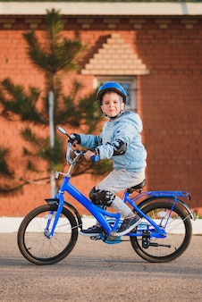 Il ragazzino in casco va in bicicletta in una giornata di sole