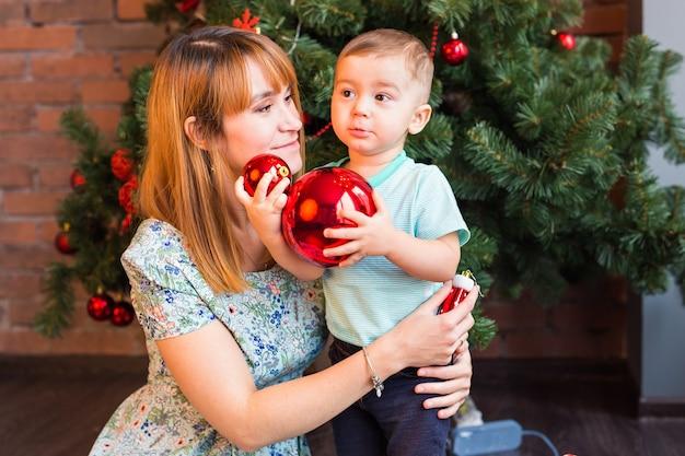 Ragazzino che aiuta la sua mamma a decorare l'albero di natale.