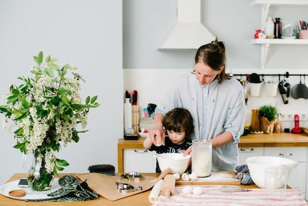 Ragazzino che aiuta sua madre con la cottura in cucina