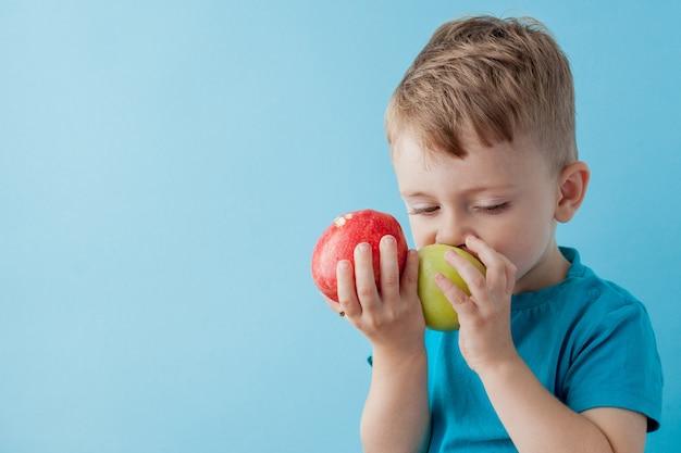 Little boy tenendo una mela nelle sue mani su sfondo blu, dieta ed esercizio fisico per un buon concetto di salute