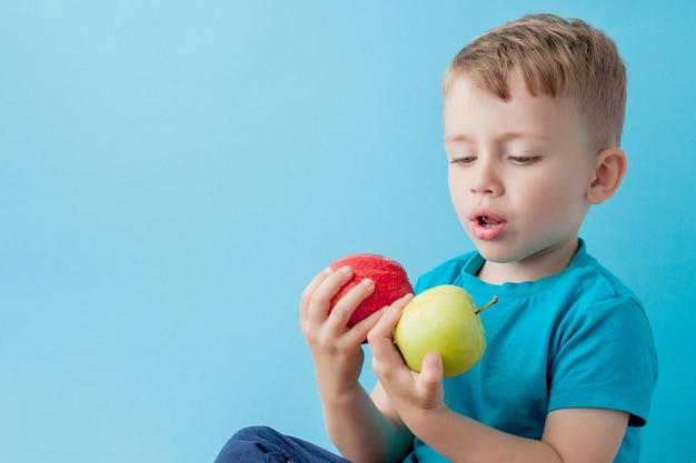 Little boy tenendo le mele nelle sue mani su sfondo blu, dieta ed esercizio fisico per un buon concetto di salute.