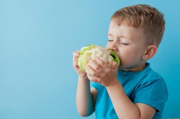 Little boy holding broccoli nelle sue mani su blu, dieta ed esercizio fisico per una buona salute