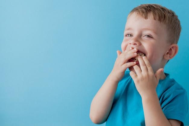 Little boy holding e mangiare una banana su sfondo blu