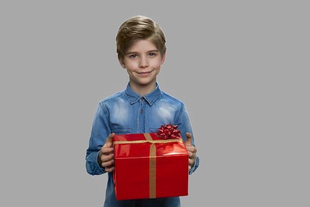 Little boy holding grande confezione regalo. elegante ragazzino tenendo presente la casella su sfondo grigio. ottieni il concetto di bonus per le vacanze.