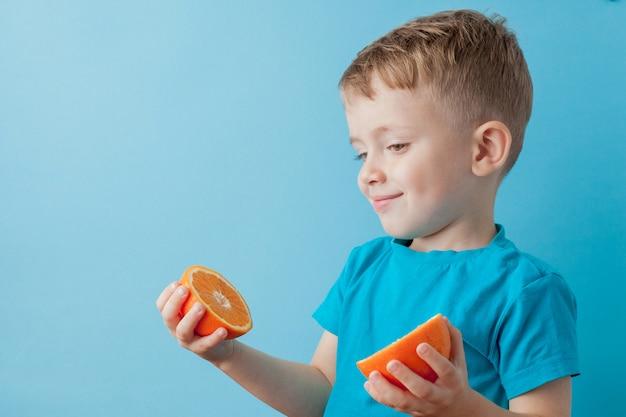 Little boy che tiene un'arancia in sue mani su fondo, sulla dieta e sull'esercizio blu per il concetto di buona salute