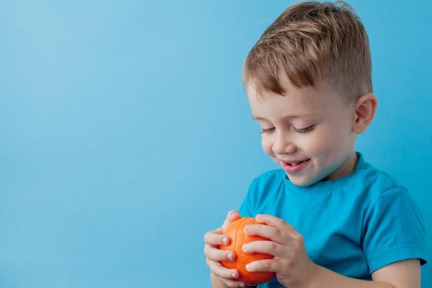 Little boy tenendo un'arancia nelle sue mani su sfondo blu, dieta ed esercizio fisico per un buon concetto di salute