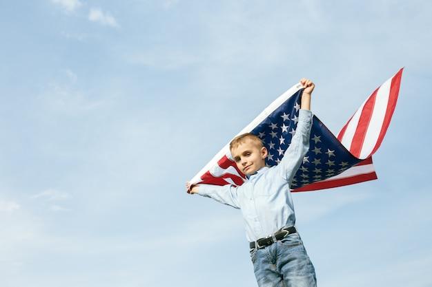 Un ragazzino tiene una bandiera degli stati uniti contro il cielo. 4 luglio festa dell'indipendenza.