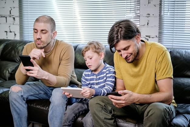 Ragazzino e coppia omosessuale che usano gadget mentre riposano sul divano