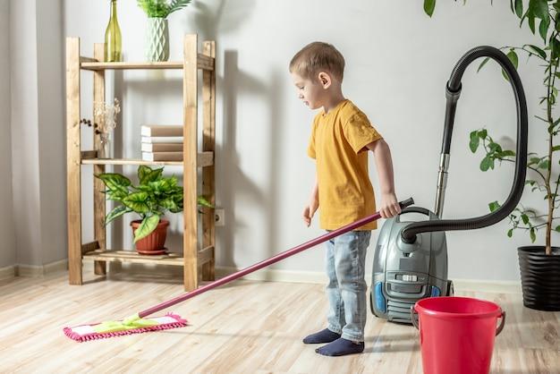 Un ragazzino sta pulendo il pavimento di una stanza usando una scopa. concetto di indipendenza, aiuto ai genitori, lavori domestici del bambino