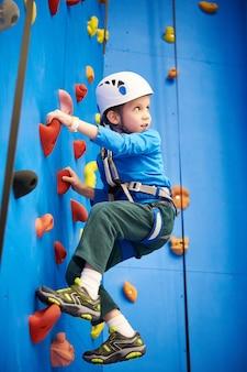 Il ragazzino sta scalando nel parco sportivo sulla parete blu
