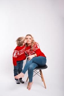 Un ragazzino sta baciando sua madre sulla guancia che è seduta sulla sedia sorridendo