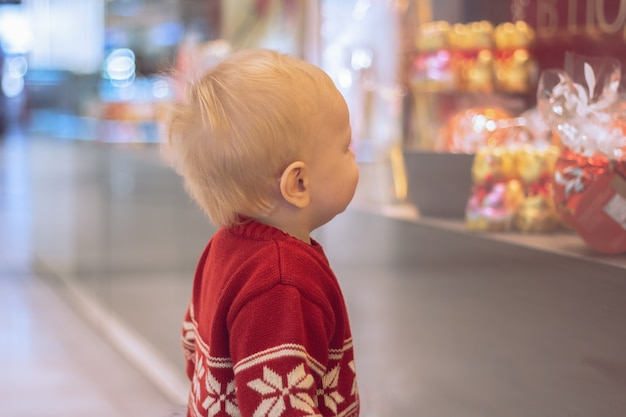 Un ragazzino sta guardando i dolci sulla vetrina di un negozio in un centro commerciale