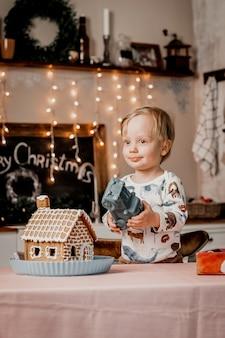 Il ragazzino sta giocando con un regalo di capodanno mentre si trova in cucina decorata con ghirlande e decorazioni natalizie