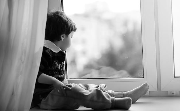 Il bambino sta leggendo un libro. il bambino si siede alla finestra e si prepara per le lezioni. il ragazzo con un libro in mano è seduto sul davanzale.