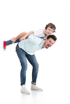 Il ragazzino sta cavalcando le spalle di papà