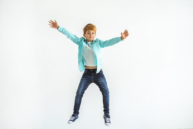 Il ragazzino che salta sullo sfondo bianco