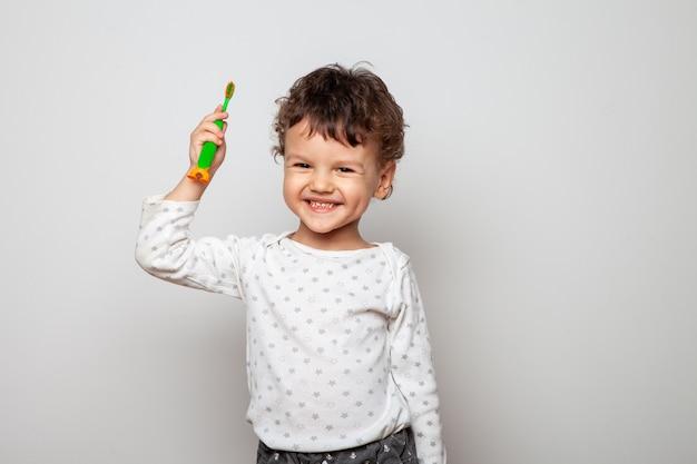 Ragazzino, il bambino è in piedi in pigiama e tiene in mano uno spazzolino da denti. dimostrazione. sguardo serio di un bambino su un bianco. procedura di igiene personale.